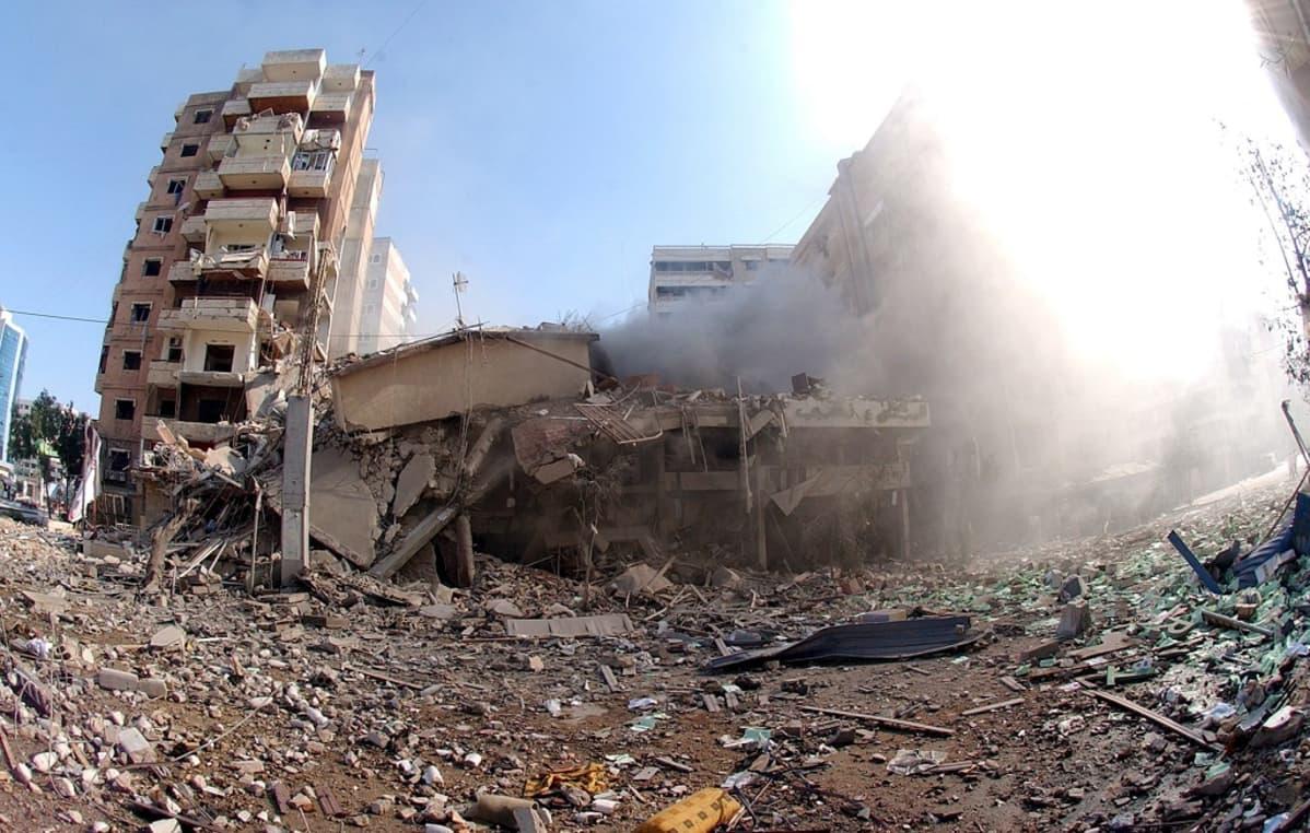 Pommituksen tuhoja. Kuvassa näkyy tuhoutunut rakennus ja räjähdyksen maahan heittämää rojua. Oikeassa laidassa leviää