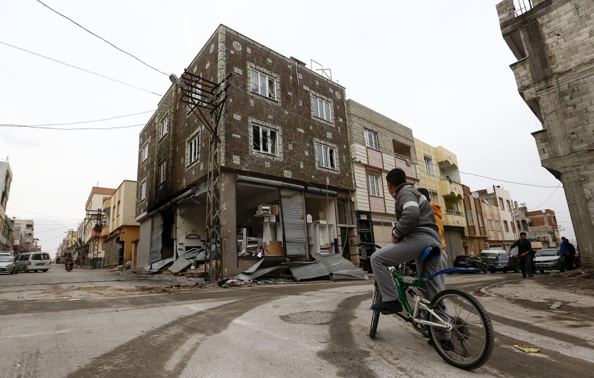Lapsi polkupyöränsä kanssa kadulla tuhoutuneen talon edessä Turkissa.