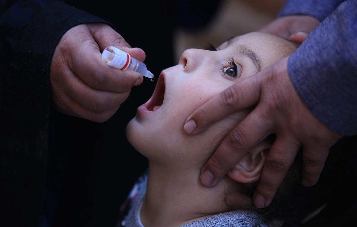 Pikkulapsen suuhun tiputetaan pienestä pullosta rokotetta.