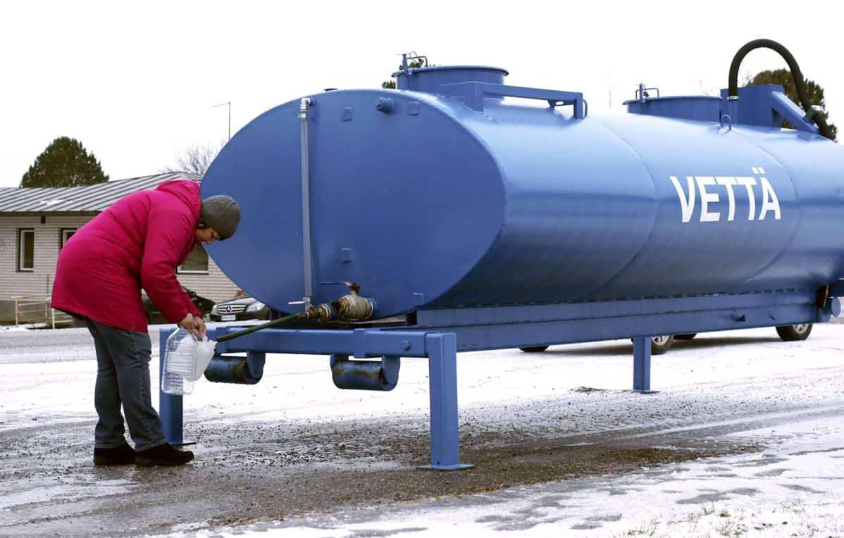 Nainen ottaa vettä vesitankista.