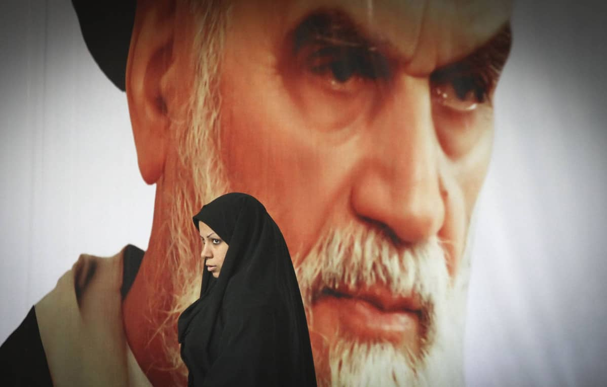 Nainen kävelee suuren Ayatollah Ruhollah Khomeini kuvan ohitse.