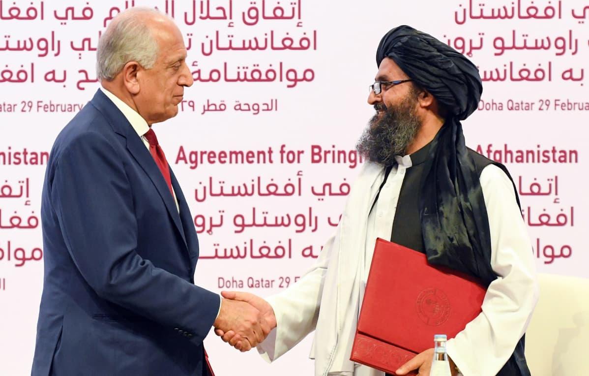 Yhdysvaltain Afganistanin erityisedustaja Zalmay Khalilzad (vas.) ja Talibanin poliittisen siiven apulaisjohtaja mullah Baradar.