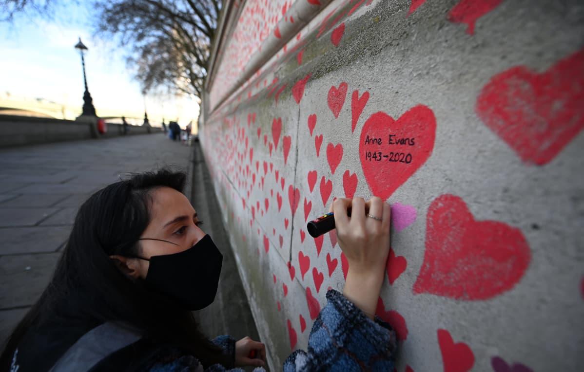 Nainen värittää punaisella tussilla sydäntä muuriin, sydämen sisällä teksti Anne Evans 1943-2020
