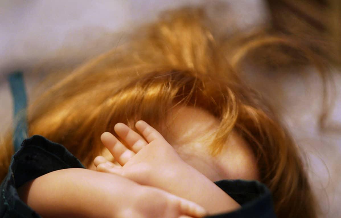 Nukke, jonka kädet peittävät kasvot.