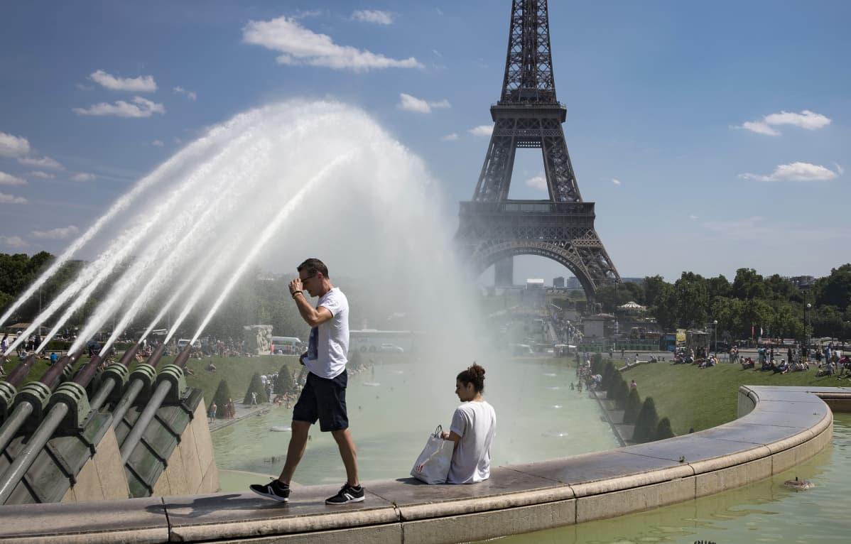 mies kävelee ja nainen istuu Eiffel-tornin edessä.