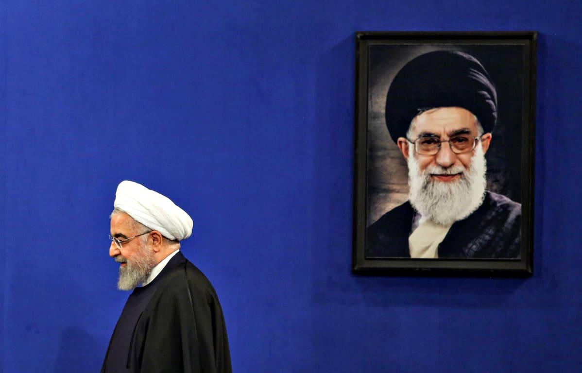 Iranin presidentti Hassan Rouhani kävelee Ali Khamenein seinällä olevan muotokuvan ohi.