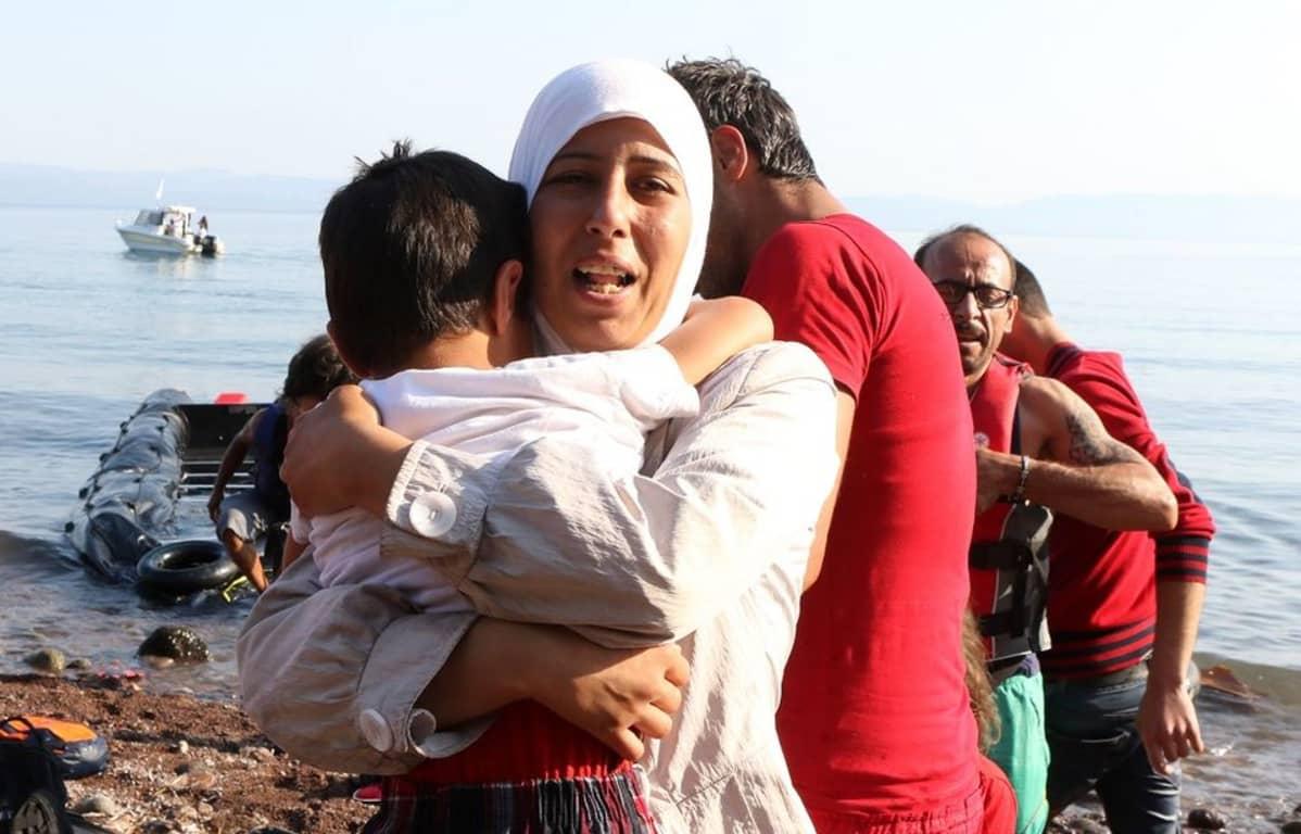 Äiti kantaa lastaan turvapaikanhakijoiden veneen rantautuessa Lesbosin saarelle elokuussa 2015. Eurooppaan pyrkijöitä saapuu erityisesti Samosin, Lesbosin ja Chiosin saarille.