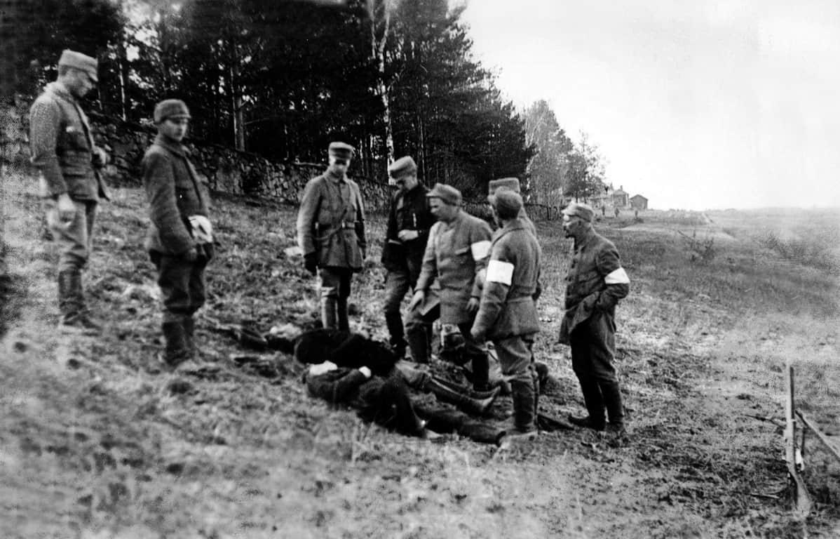 Pohjois-Savon rykmentin suojeluskuntalaiset tarkastelevat teloittamiensa punakaartilaisten ruumiita.