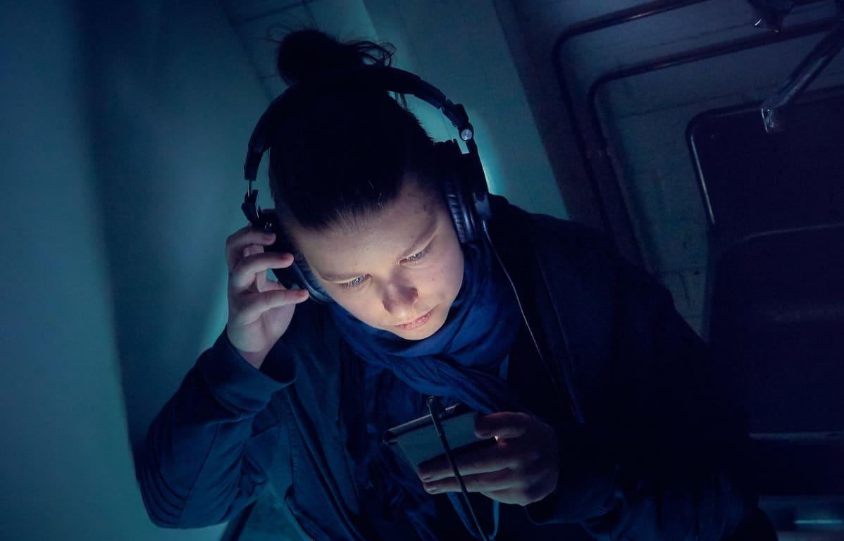 Nuori nainen kuuntelee podcastia matkapuhelimesta