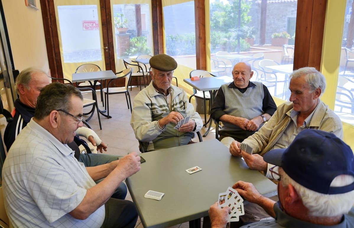 Miehet pelaavat korttia. Acciarolin kylän miehet kokoontuvat iltapäivisin pelaamaan korttia ja juoruamaan.