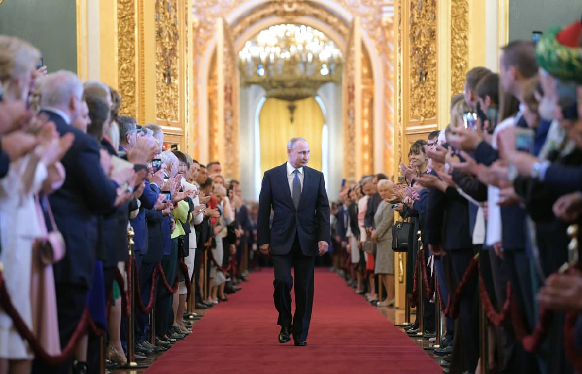 presidentti Vladimir Putin kävelee kultaisessaa salissa, ympärillä yleisöä.