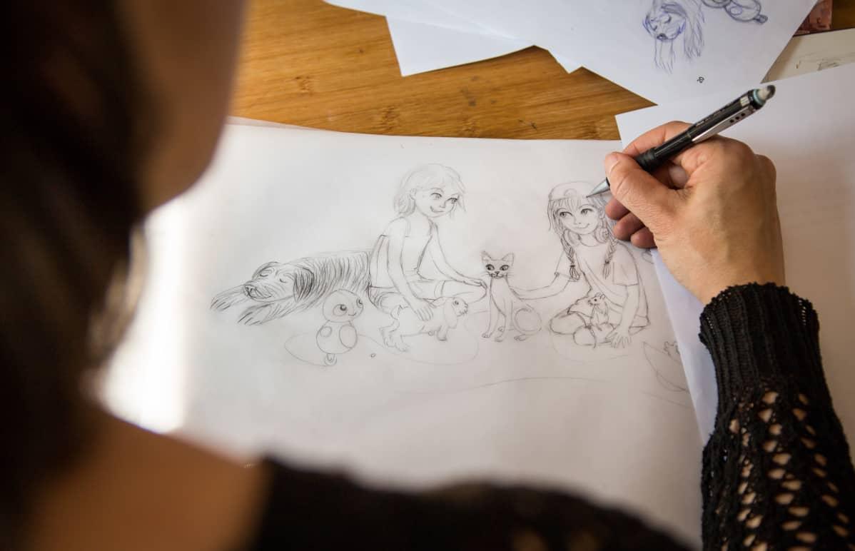 Riina Kaarla piirtävää lastenkirjaa kotonaan.