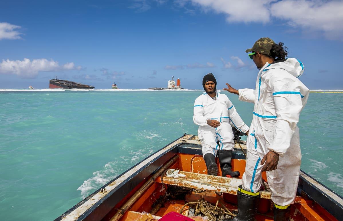 Mahebourgin kylästä kotoisin olevat vapaahetoiset hakivat maanantaina öljyn imeyttämiseen tarkoitettuja käsintehtyjä työkaluja. Taustalla öljyvuodon aiheuttanut japanilainen rahtilaiva.