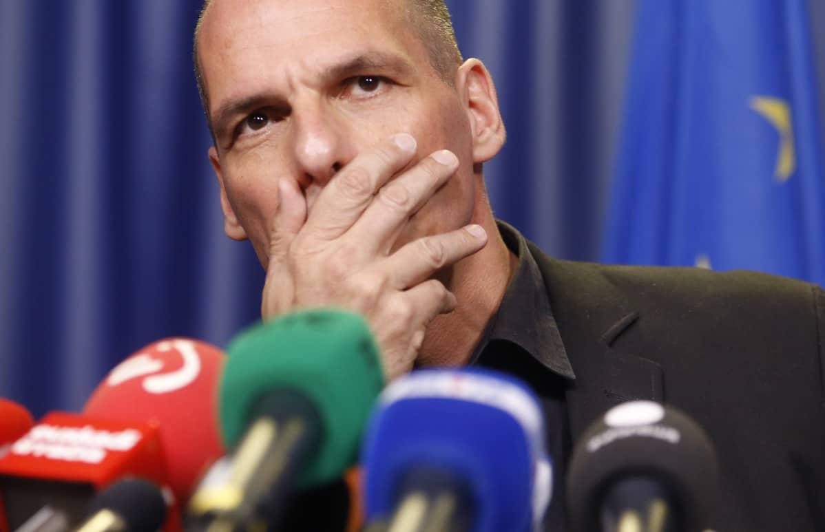 Mies käsi suunsa edessä ja joukko mikrofoneja.