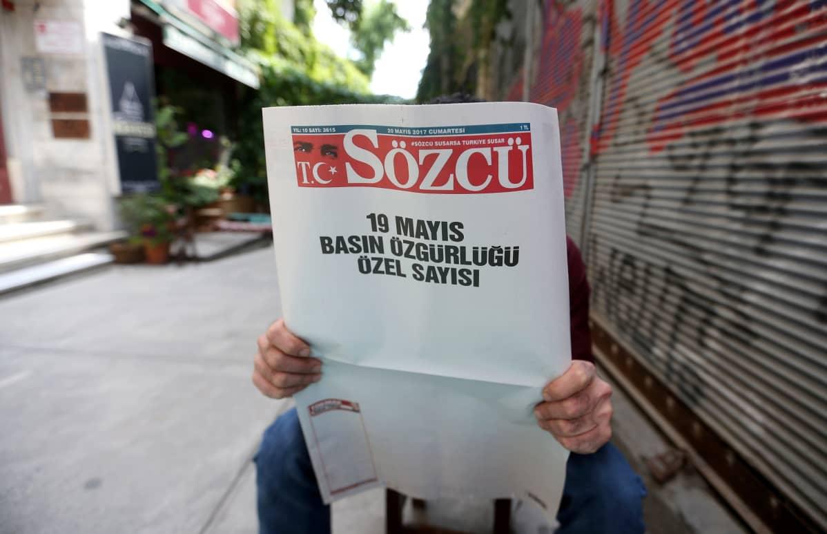 Mies pitelee lehteä, jonka etusivu on tyhjä lehden logoa lukuunottamatta.