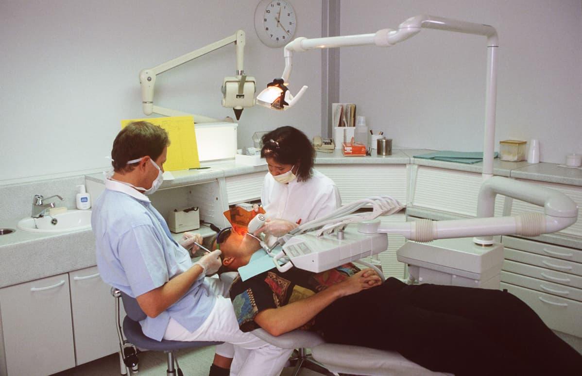Hammaslääkäri ja hammashoitaja työssään.