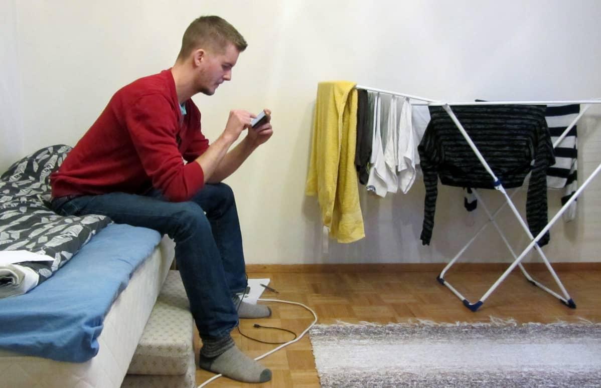 Riku Forsell istuu sängyllä ja selaa puhelinta