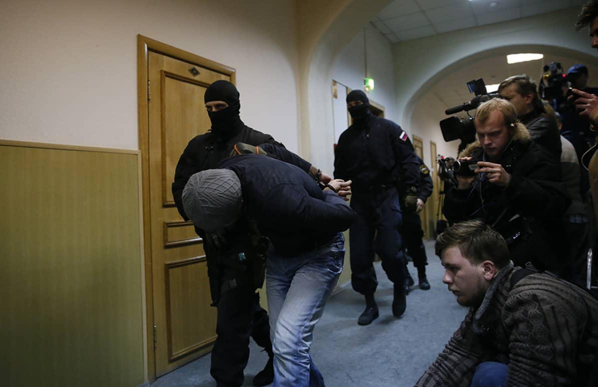 Poliisit saattoivat Boris Nemtsovin murhasta epäiltyä miestä oikeuteen Moskovassa 8. maaliskuuta.