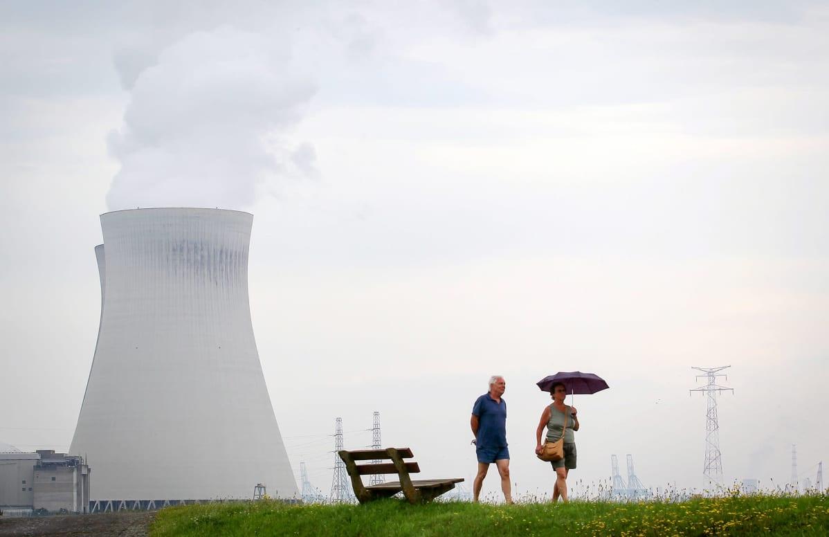 Ett par går vid ett kärnkraftsverk i Belgien.