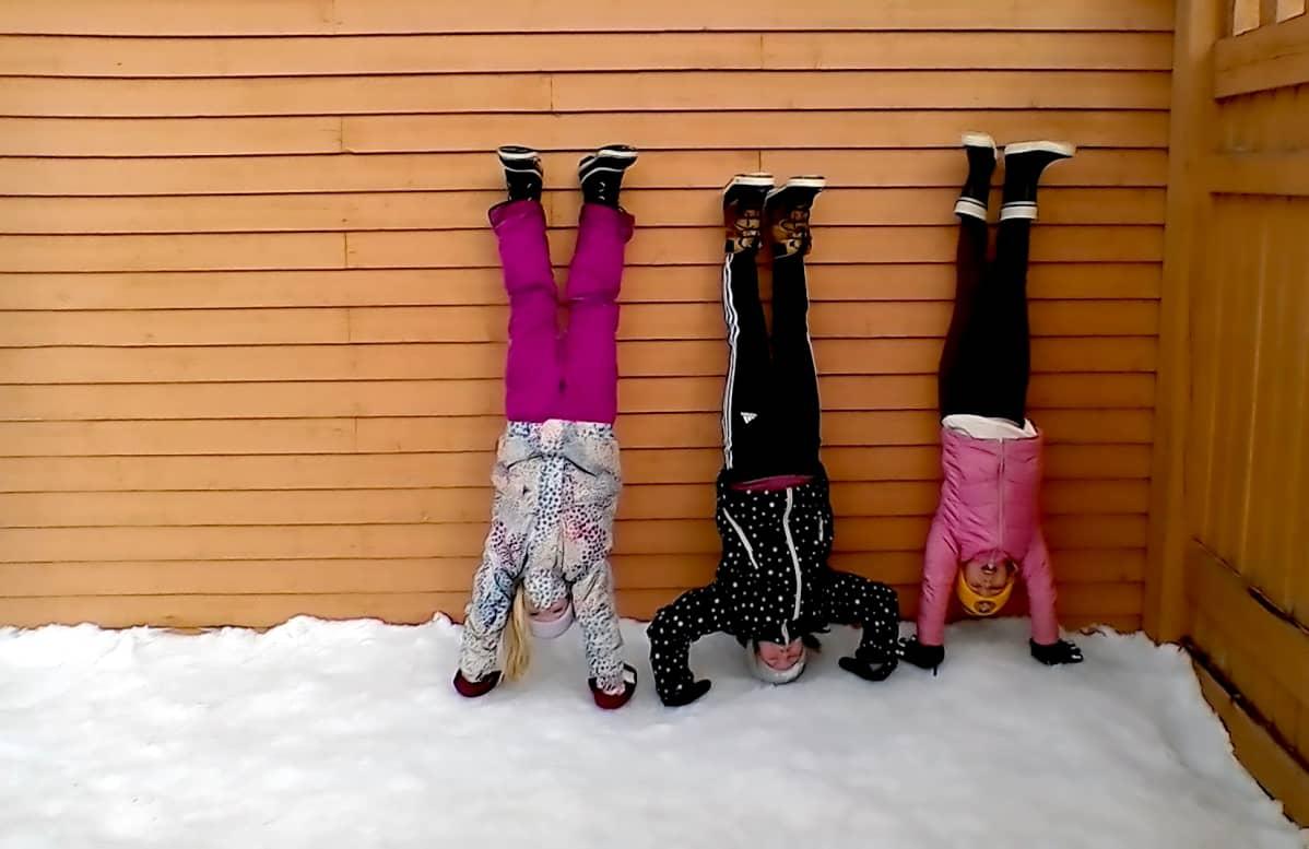 Kuvassa kolme lasta seisoo käsillään ulkona.