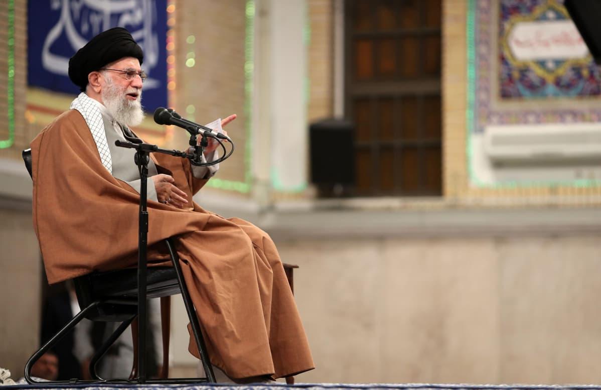 Ali Khamenei istuu tuolilla ja pitää puhetta.