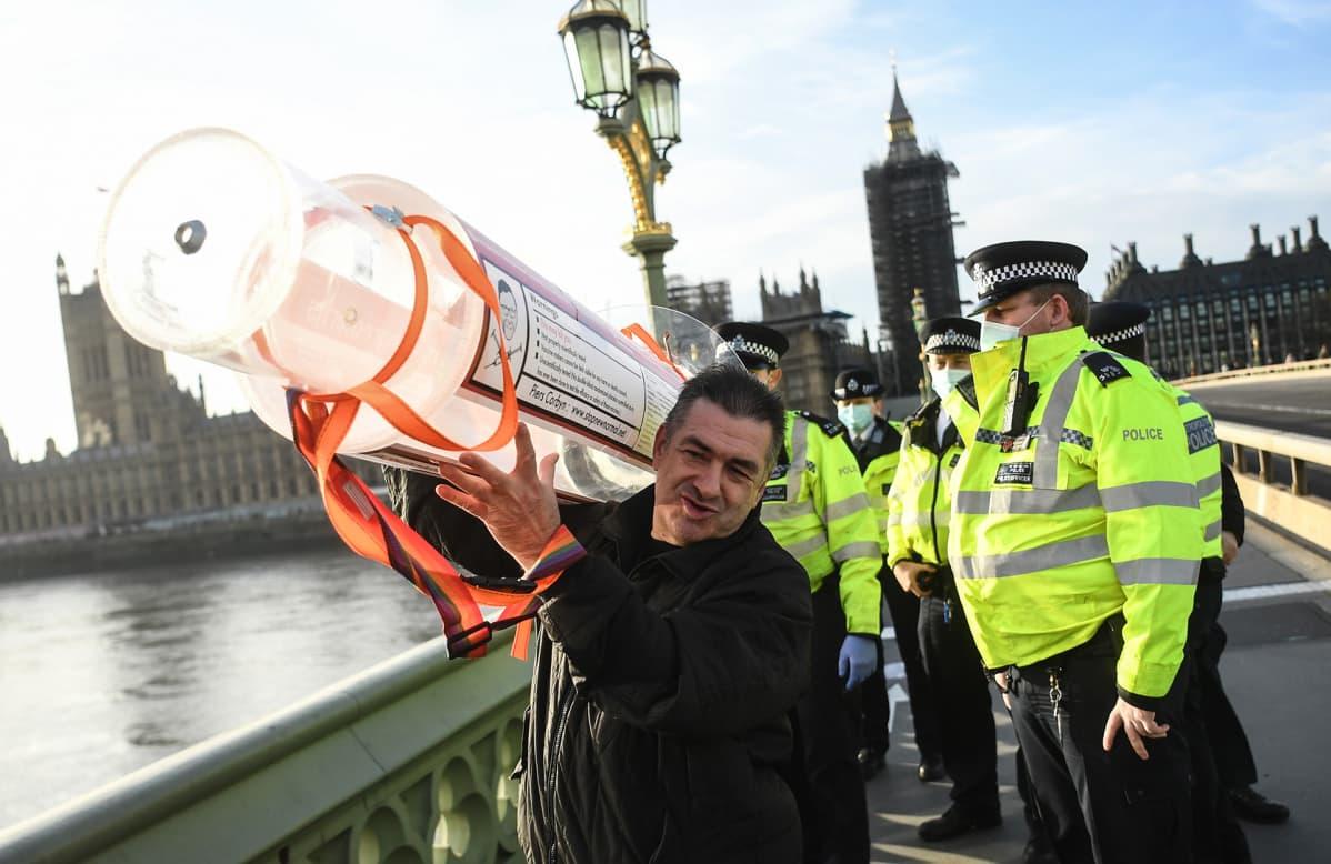 Rokotusten vastainen mielenosoittaja kantaa olallaa jättiläismäistä ruiskua ja poliisit seuraavat vierestä.