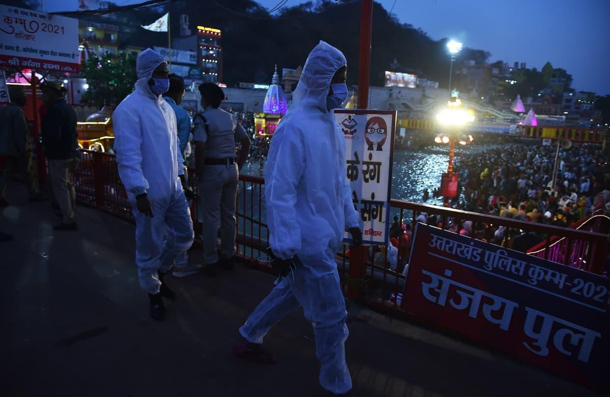 Suojavarusteisiin pukeutuneita intialaisia terveysviranomaisia Kumbh Mela -tapahtumassa Haridwarissa.