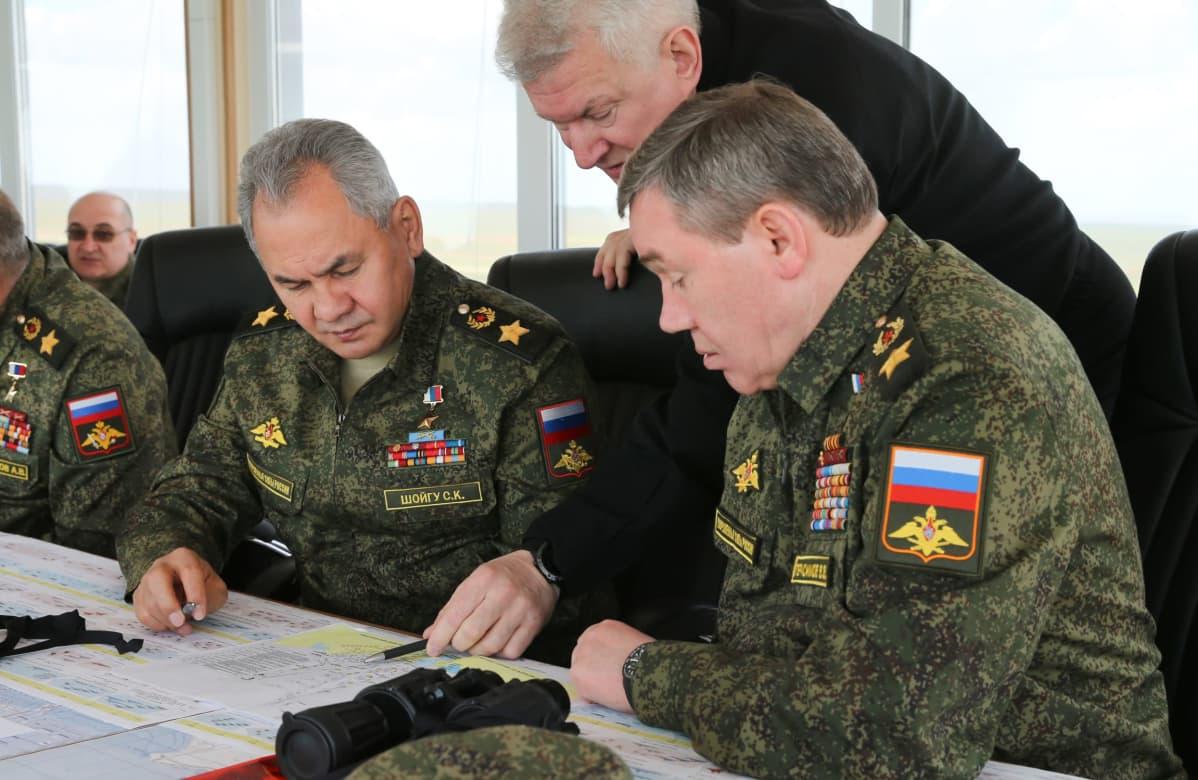 Sergei Šoigu ja Valeri Gerasimov istuvat pöydän ääressä maastokuvioisissa univormuissa ja tutkivat vakavina karttaa. Kollmas mies kurkottaa heidän välistään ja näyttää kynllä kohtaa kartasta.