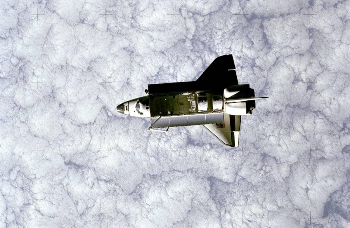 Avaruussukkula Challenger satelliitin kuvaamana . Alla Maan paksu pilviverho.