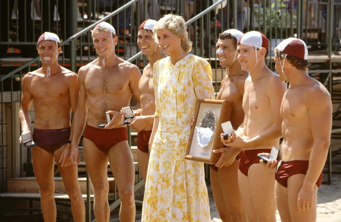 Prinsessa Diana uimahousuisten miesten keskellä.
