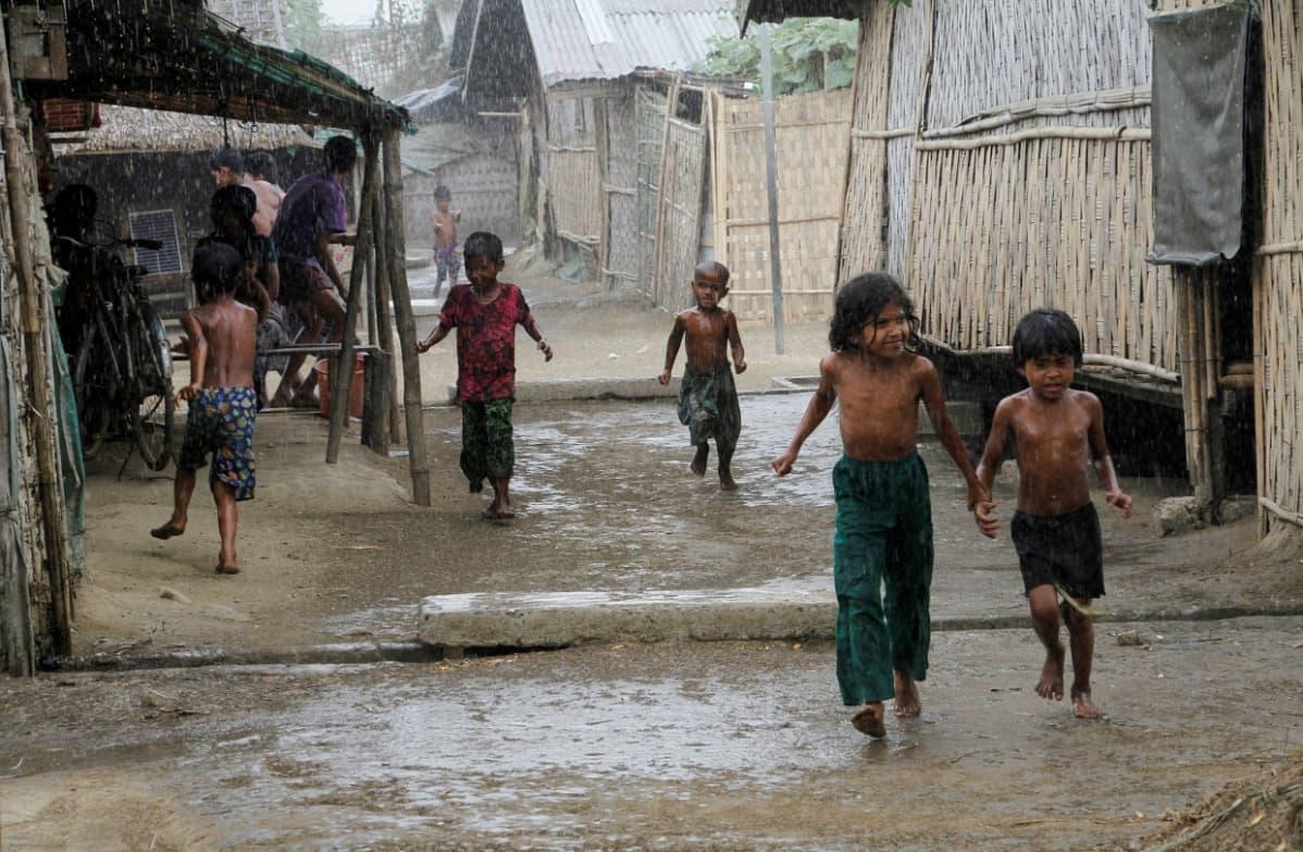 Lapsia juoksee sateessa. Bamburakenteisia taloja kylän raitilla.