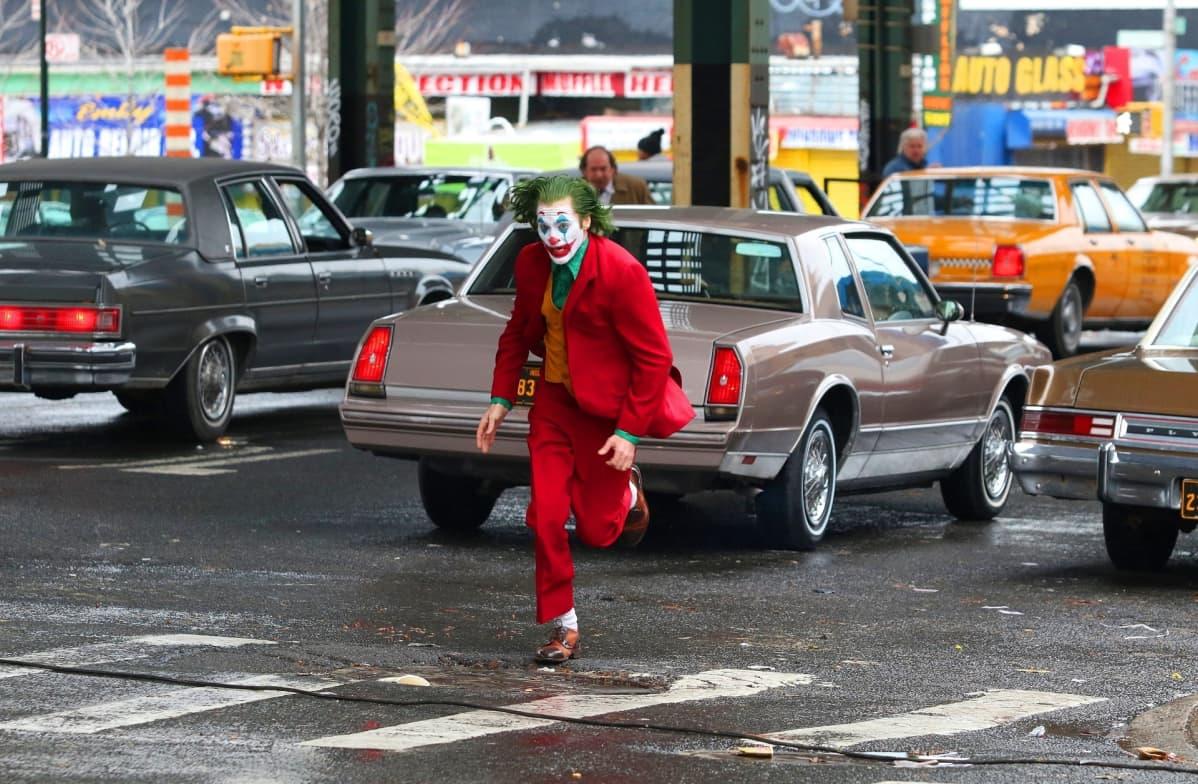Jokeriksi maskeerattu Joaquin Phoenix juoksee kadulla.