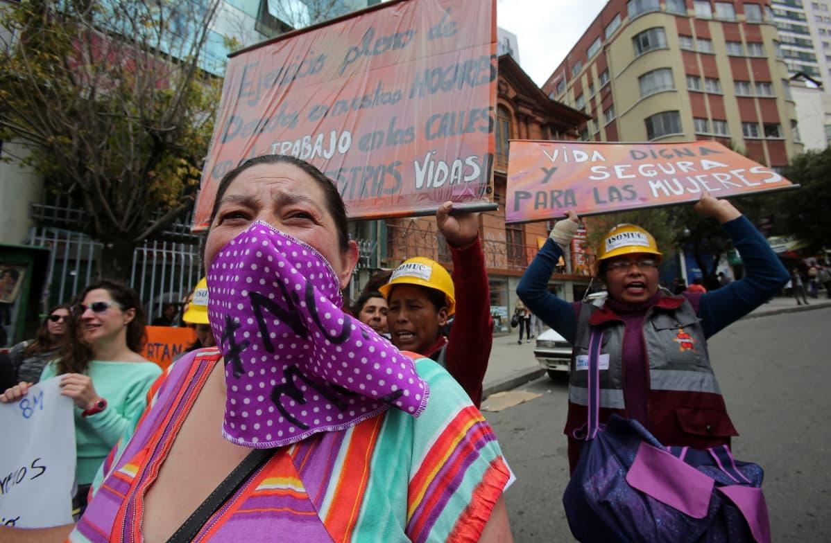 Mielenosoittajia, osalla työmiesten kypärät päässään.