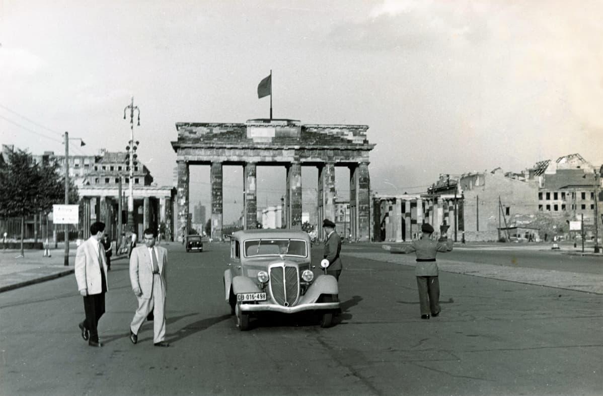 Auto on pysähtyneenä tarkastuspisteelle. Yksi poliisi on auton luona, toinen ohjaa liikennettä. Kaksi miestä vaaleissa puvuntakeissa ohittaa pistettä. Taustalla näkyy Brandenburgin portti, jonka yllä liehuu iso punalippu.