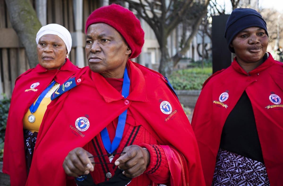 Punaisiin pukeutuneita naisia mielenosoituksessa.