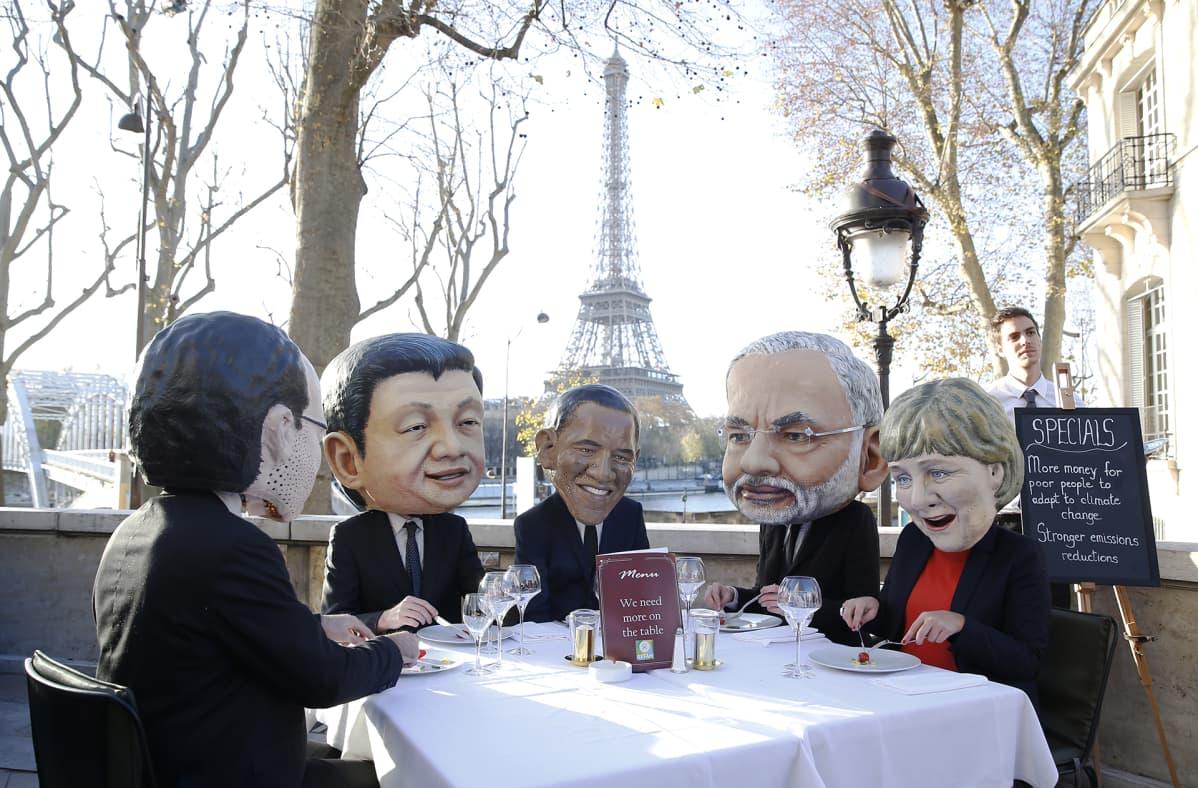 Neljä henkilöä suuret suurjohtajia esittävät maskit päässään syömästä lounasta.