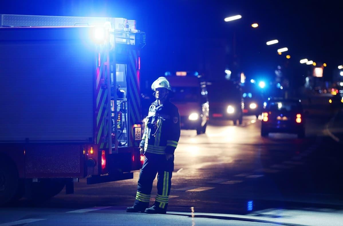 Palomies hälytysajoneuvojen edessä.