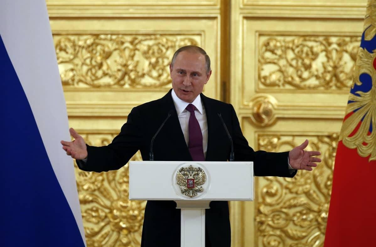 Putin puhuu korokkeen takaa ja levittää juuri käsiään. Putinilla on tumma asu ja viininpunainen kravatti. Taustalla näkyy suuri kullattu ja koristeltu ovi ja kuvan oikeassa ja vasemmassa reunassa Venäjän liput. Korokkeessa on Venäjän vaakunaeläin, kaksipäinen kotka.