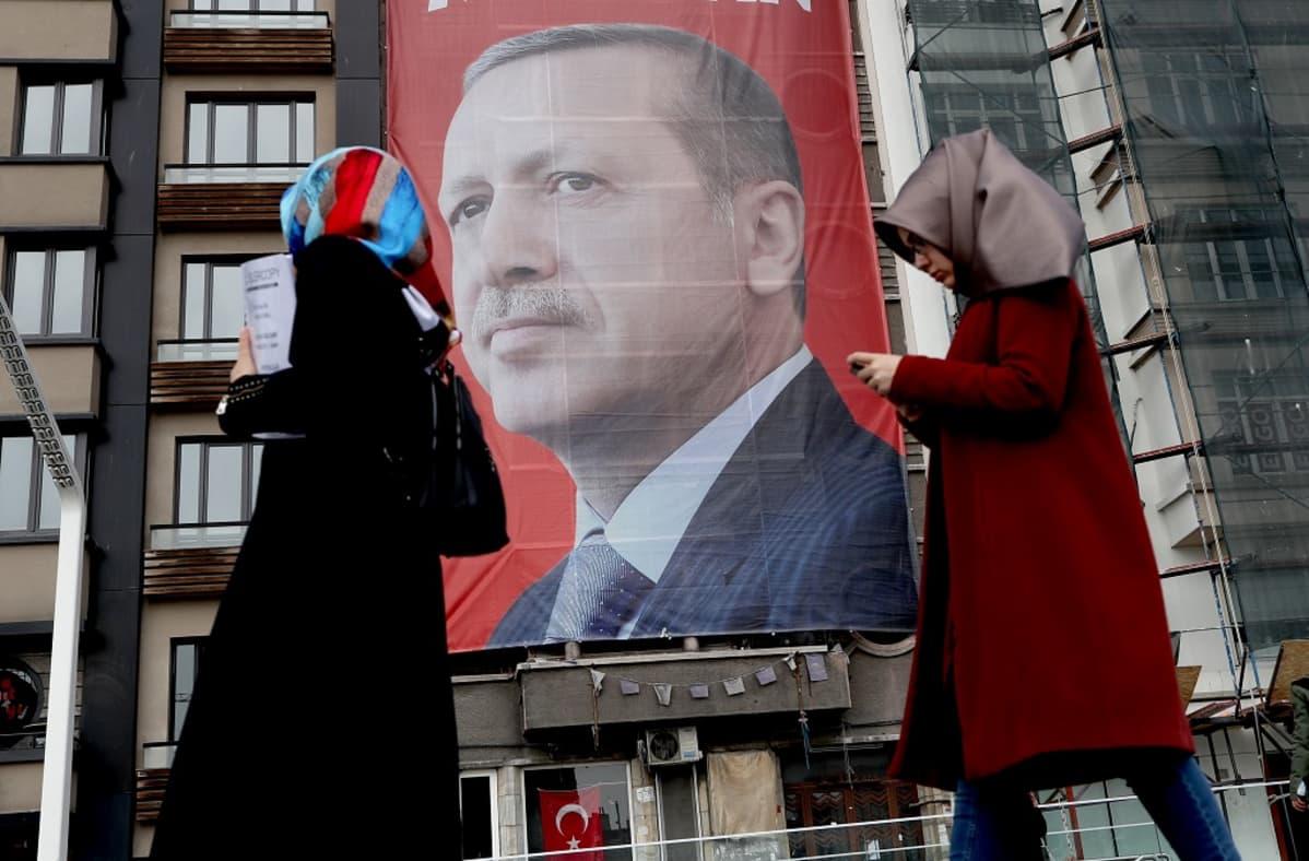 Isossa katujulisteessa Erdoğanin potrettikuva, ohi kävelee kaksi naista huivit päässä.