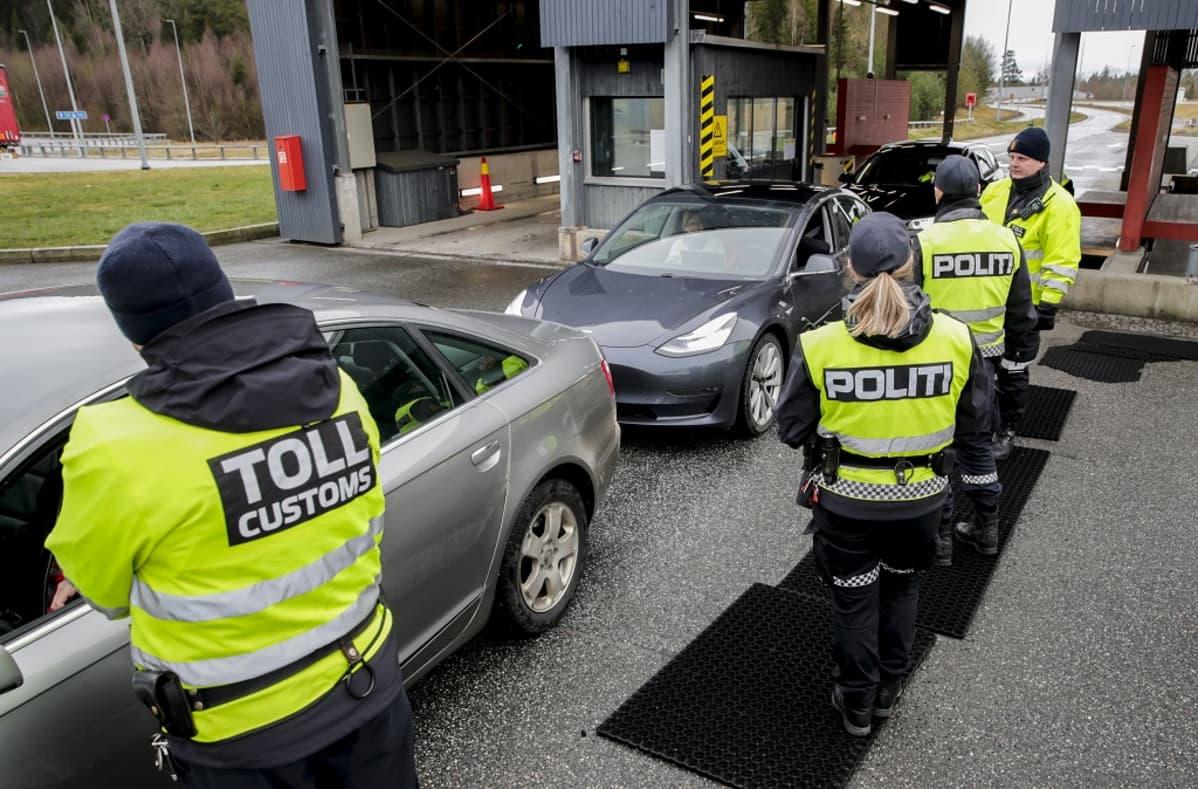 Neljä keltaisiin liiveihin pukeutunutta tulli- ja poliisimiestä tarkistamassa autojonoa.
