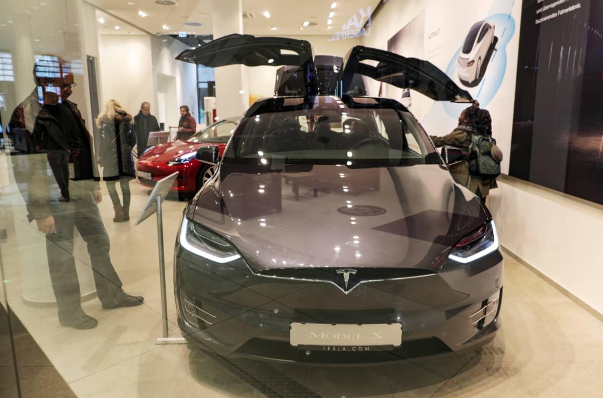 Kävijät katselevat Teslan autoa