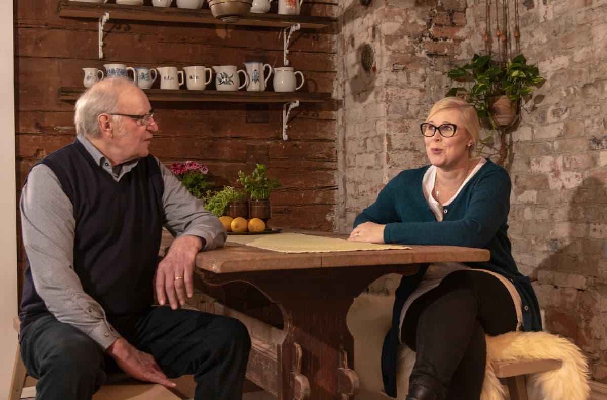 Ollilan vanhaisäntä Heikki Ollila ja hänen tyttärensä Elina Töllinen tuvan pöydän ääressä.