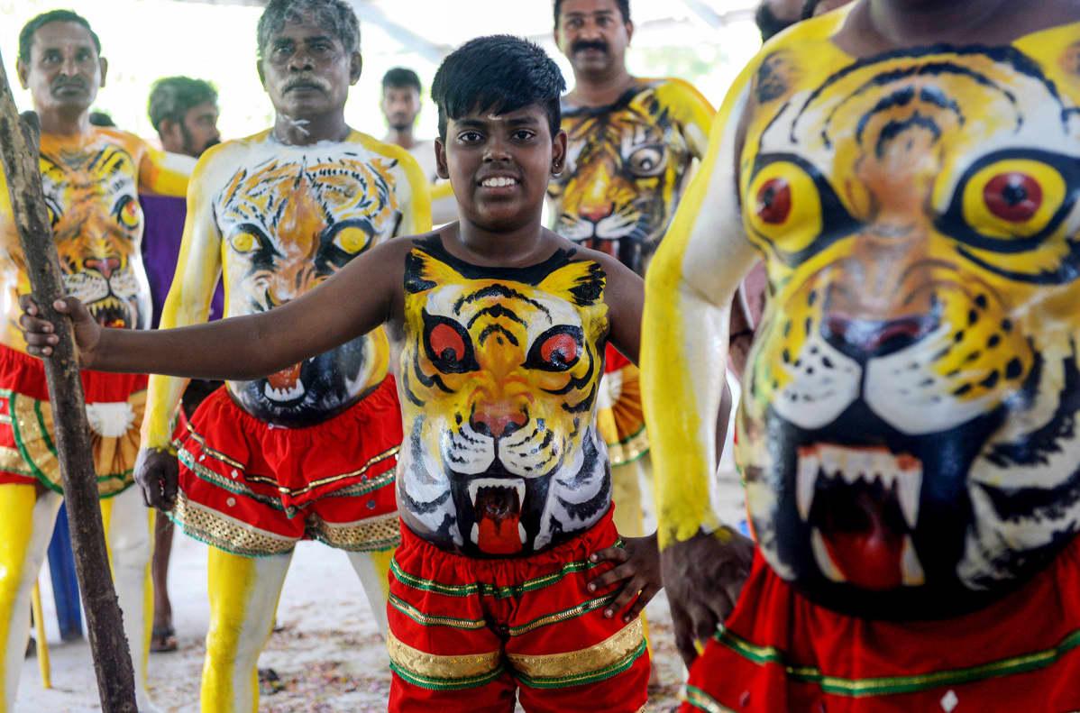 Poika ja miehiä tiikerimaalaukset vartaloillaan.