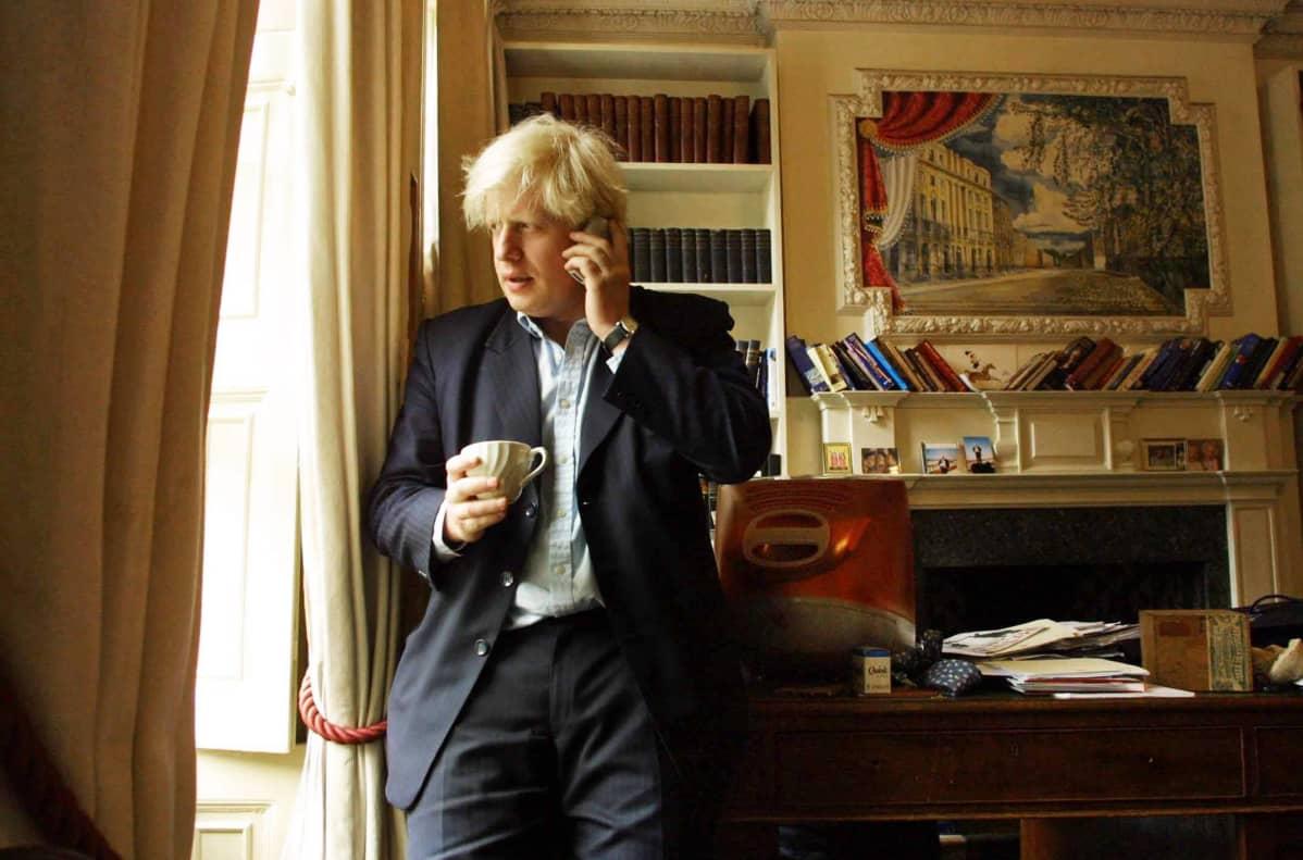 Boris Johnson toimistossa puhuen puhelimeen.