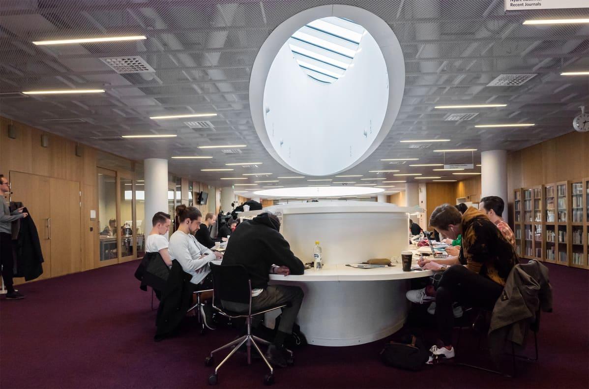 Opiskelijat lukevat kirjastossa.