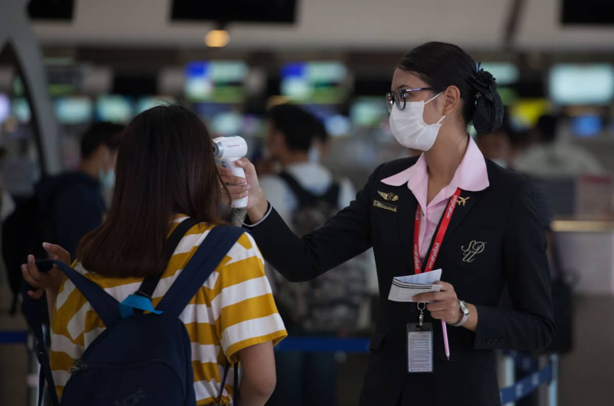 Lentokenttävirkailija mittasi matkustajalta kuumetta Suvarnabhumin lentokentällä Thaimaassa.