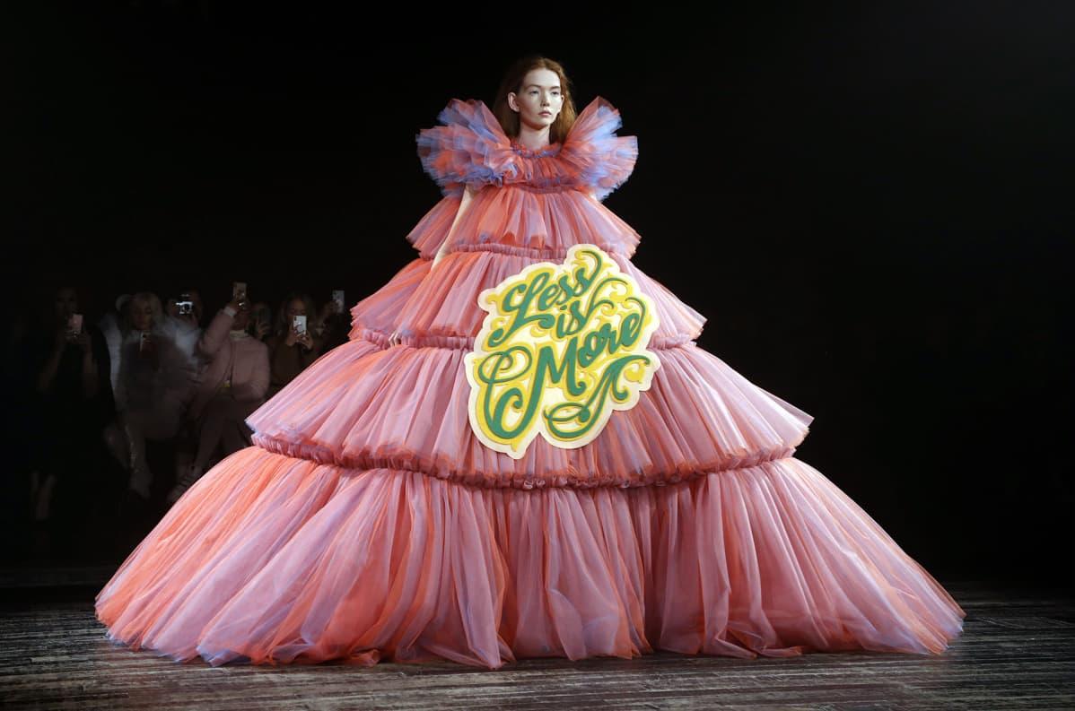 Malli valtavassa mekossa, jossa lukee 'Less is more'.