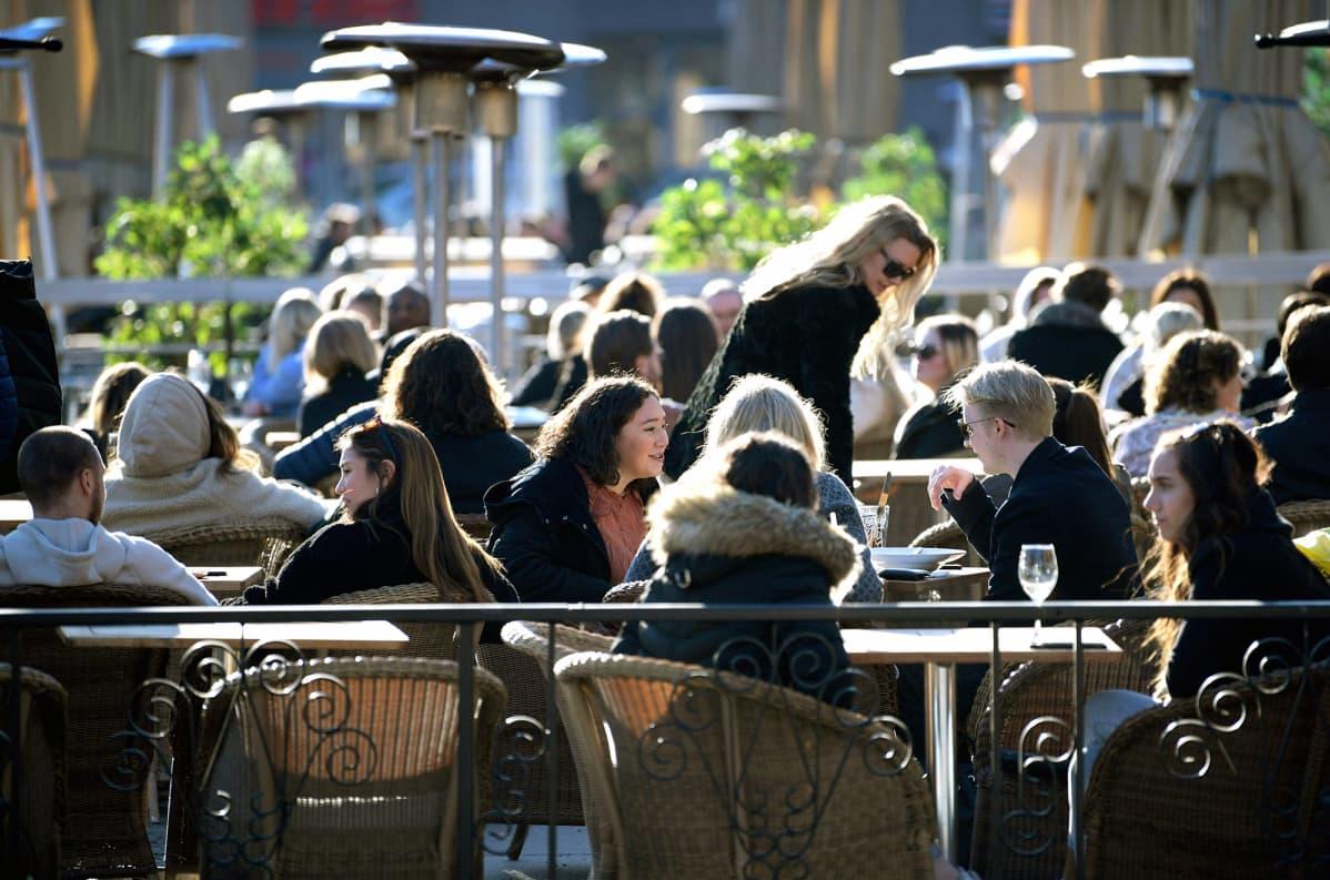 Ihmiset istuvat ulkona ravintolan terassilla Tukholmassa.