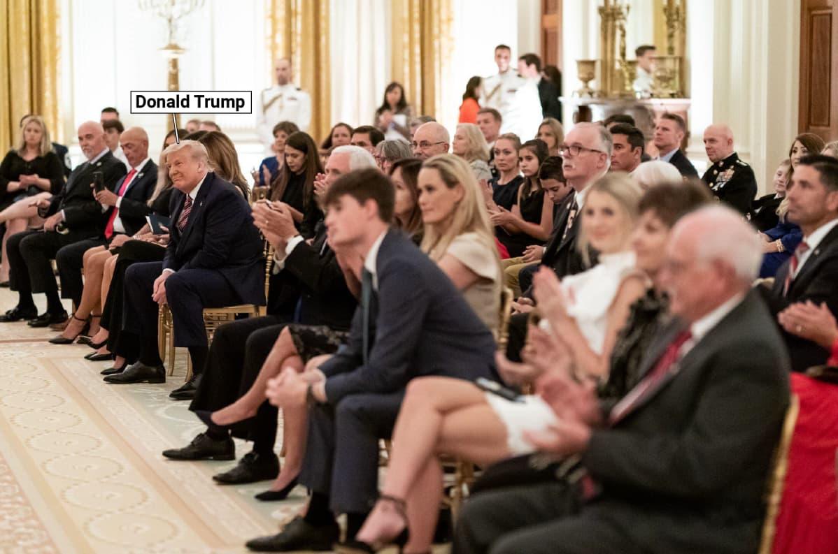 Trump yleisön joukossa.