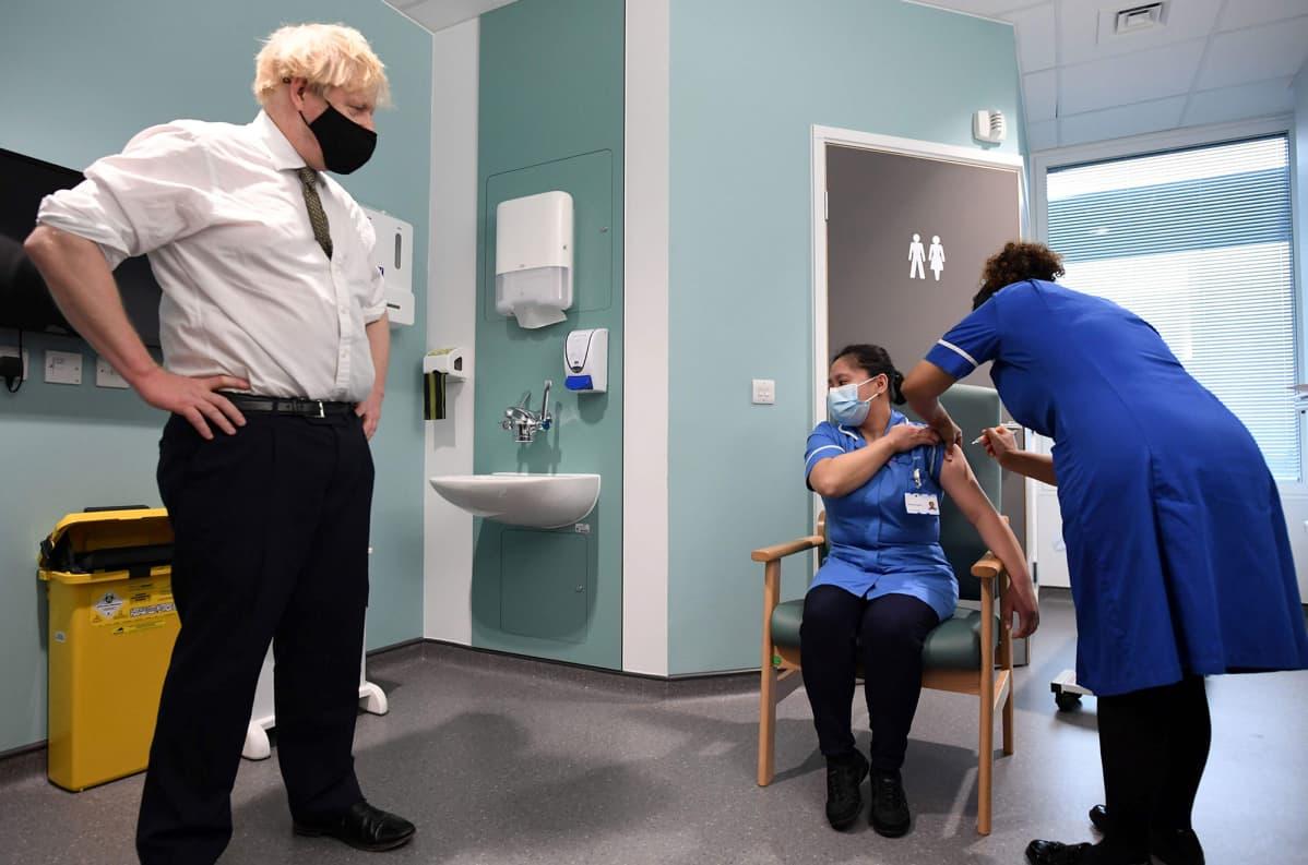 Britannian pääministeri Boris Johnson seuraa kun sairaanhoitaja rokottaa toisen sairaanhoitajan.